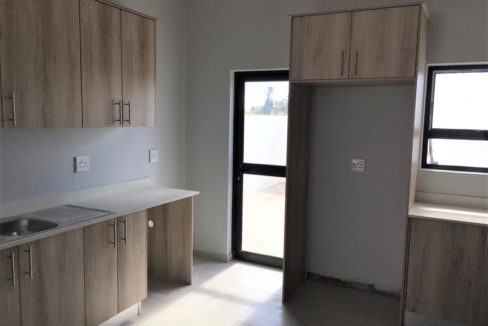 Kitchen with alluminium back door and space in corner for tumble dryer or washing machine