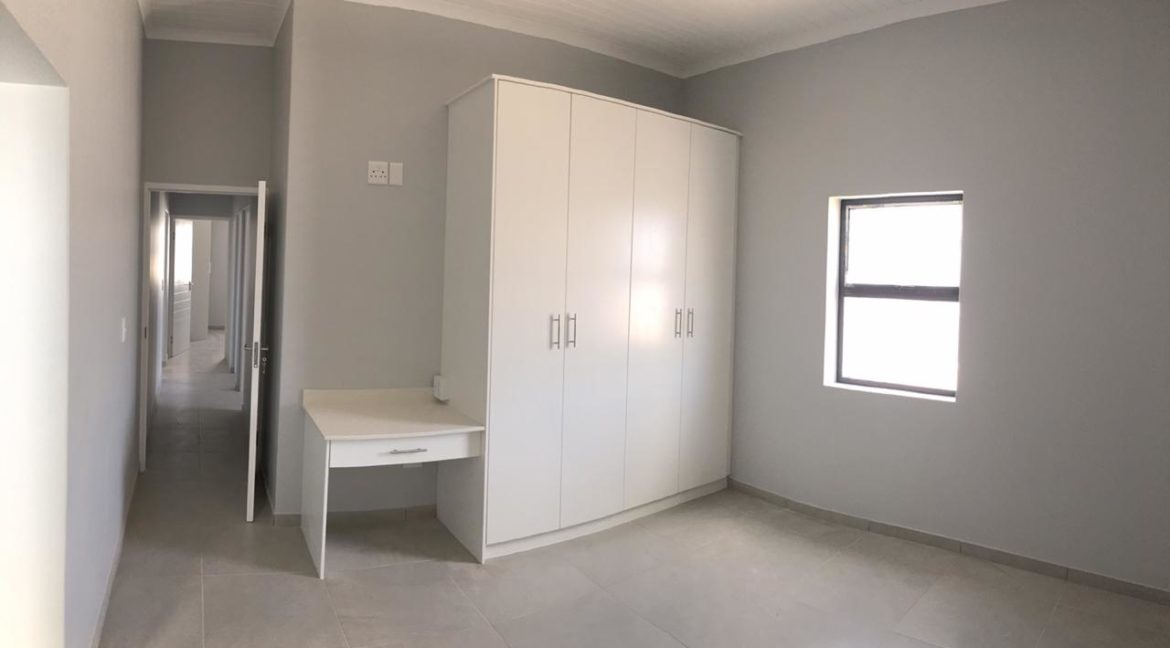 Main bedroom with built-in cupboards and dressertable