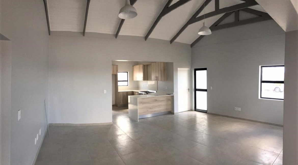 Open plan view from indoor braai accross lounge to kitchen area