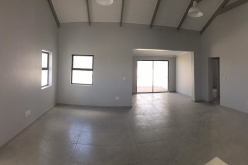 View from kitchen over open plan lounge and braai area with sliding door